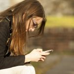 Woman suffering from text neck bends over her phone in Waterloo
